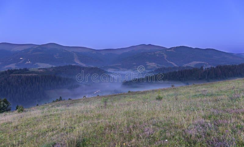 En grön äng och en grå lockig dimma på en kulle i bakgrunden av de Carpathian bergen i ottan royaltyfri foto