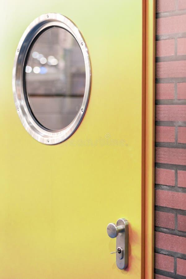 En grön dörr med ett runt fönster i en tegelstenvägg arkivbild