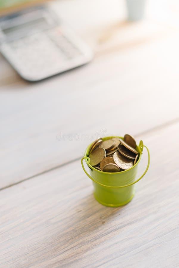 En grön hink med mynt på en träbakgrund äganderätt för home tangent för affärsidé som guld- ner skyen till fotografering för bildbyråer