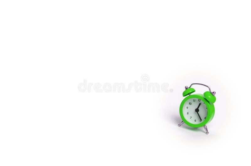 En grön ringklocka på en vit bakgrund Begreppet av tid och planläggningen Forntiden, framtiden och gåvan minimalism Fre royaltyfri fotografi