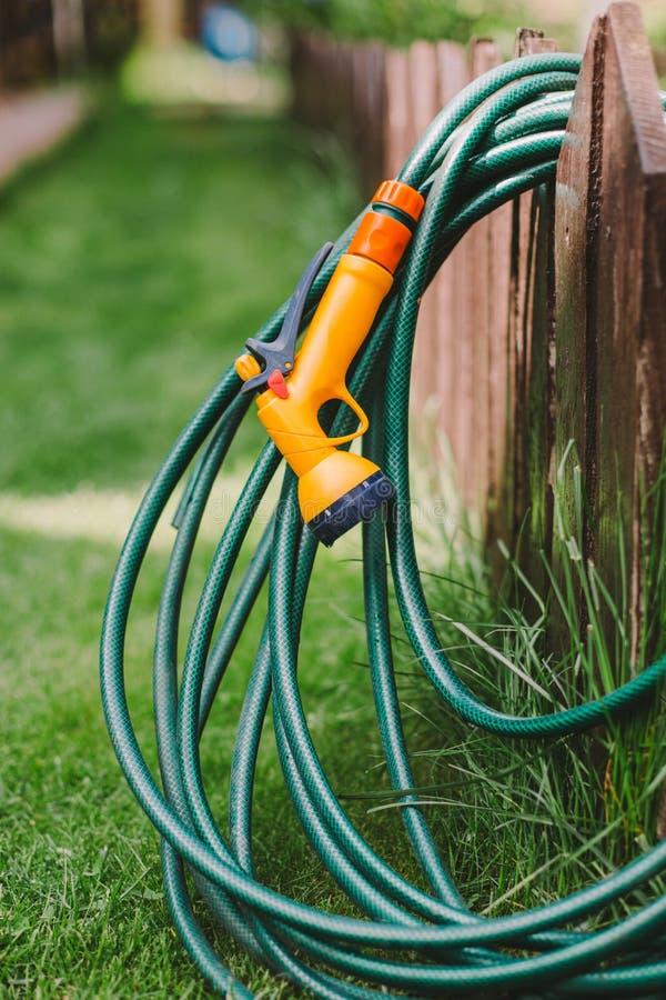 En grön rubber trädgårds- slang med dysan arkivfoton