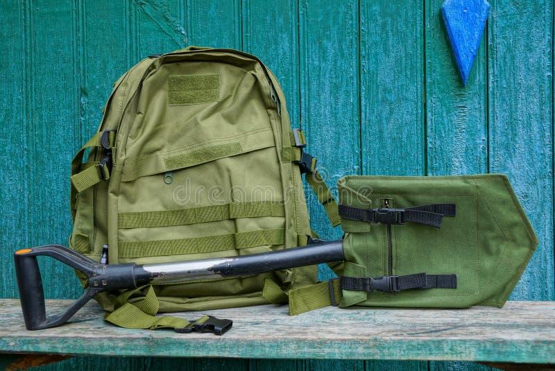 En grön ryggsäck och en skyffel i ett fall på en tabell mot en trävägg royaltyfri fotografi