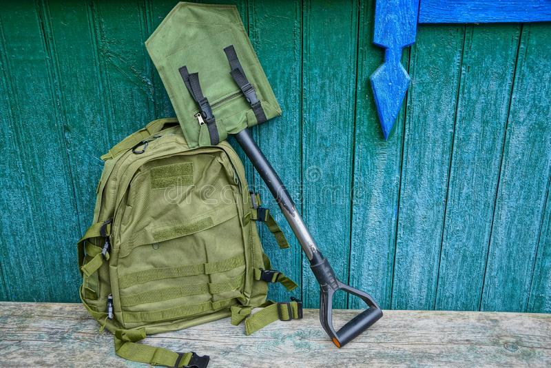 En grön ryggsäck och en skyffel i ett fall på en tabell mot en trävägg arkivbilder