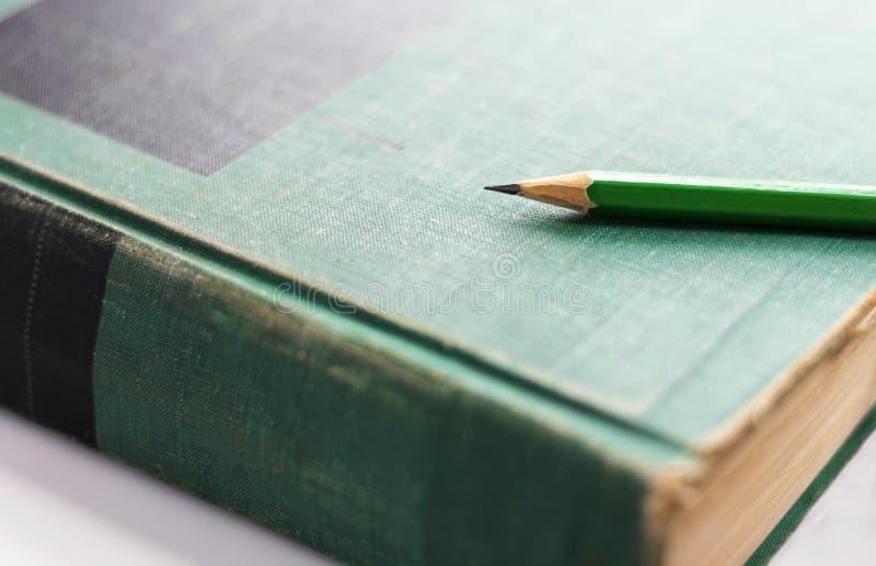 En grön träblyertspenna förläggas på inbundna boken eller läroboken Sel royaltyfri foto