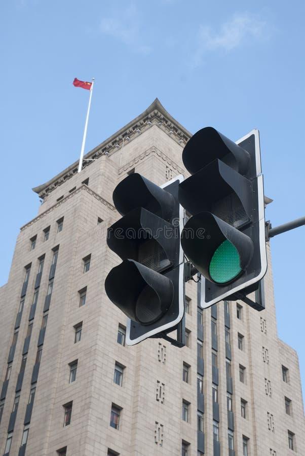 En grön trafiksignal i frong av en gammal byggnad av shanghai royaltyfria foton