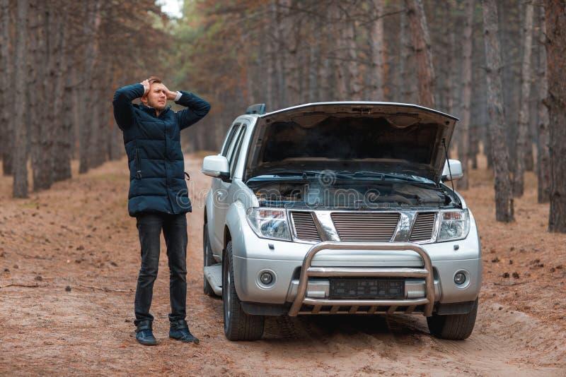 En grabb är det frustrerade hållande huvudet, medan stå nära en bruten bil med en öppen huv i röken i höstskogen fotografering för bildbyråer