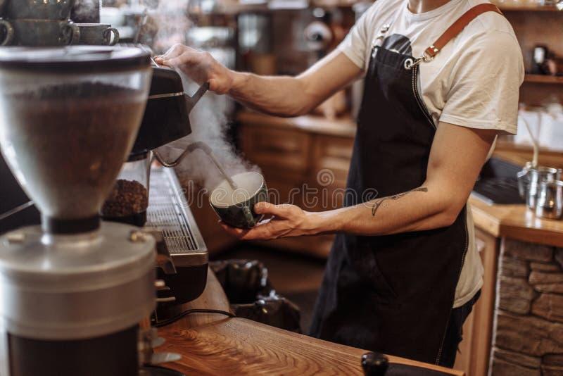 En grabb häller varmvatten i koppen i cafeterian royaltyfri foto