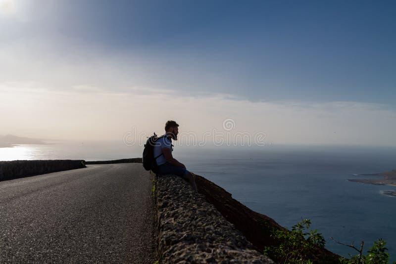 En grabb i sommarkläder sitter på ett stenstaket och ser en närliggande ö i havet royaltyfria foton