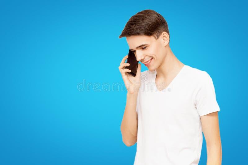 En grabb i en vit T-tröja som talar på telefonen på en blå isolerad bakgrund, snacksalig ung man royaltyfri fotografi