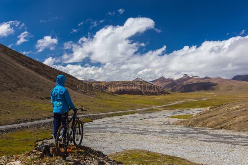 En grabb med en cykel på bakgrunden av höga berg Suek passerande kyrgyzstan arkivbild