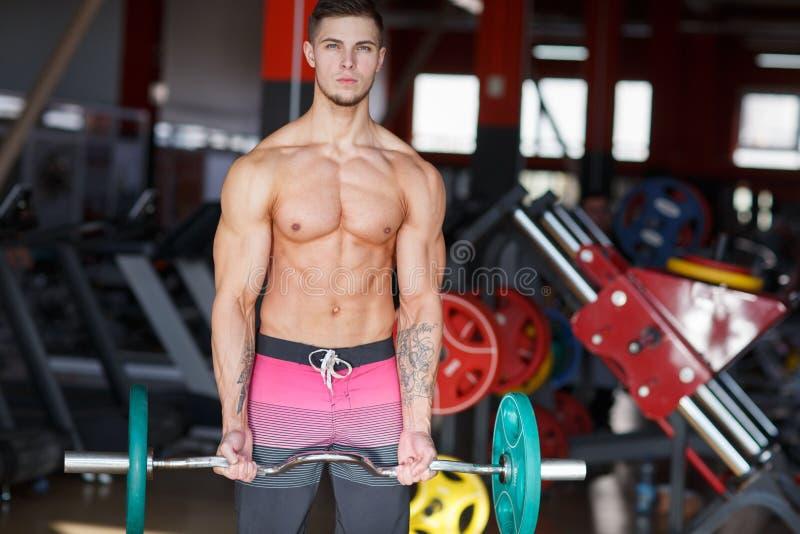 En grabb med enformad stång med pannkakor som gör övningar på en suddig bakgrund av idrottshallen arkivfoto
