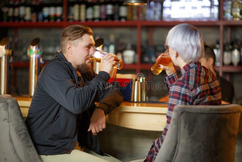 En grabb med ett skägg och en flicka med kort blont hår som sitter i en stång och dricker öl inomhus fotografering för bildbyråer