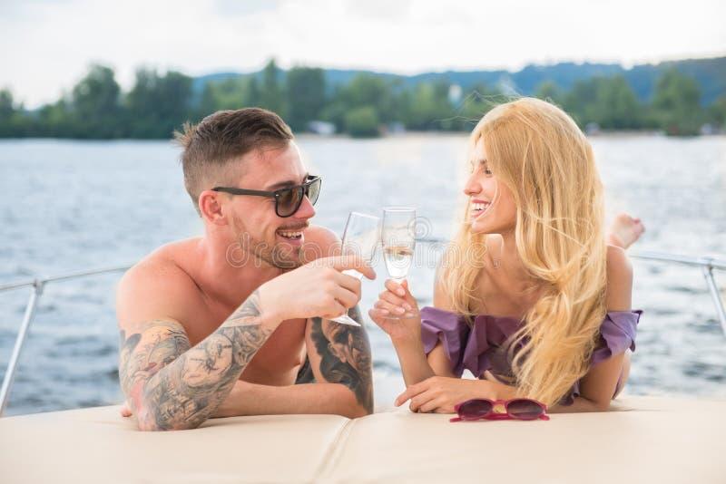 En grabb med en flicka dricker champagne på en yacht royaltyfri fotografi