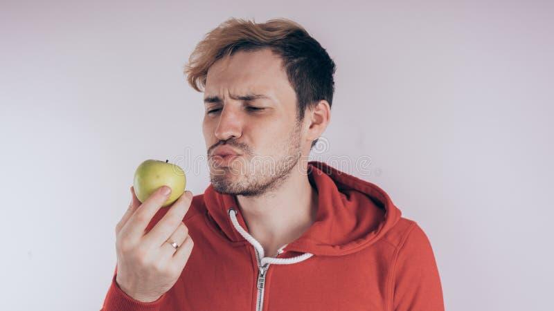 En grabb med en gladlynt framsida rymmer en gröna Apple, på en vit bakgrund Begreppet av förälskelse av den sunda fooen royaltyfri foto