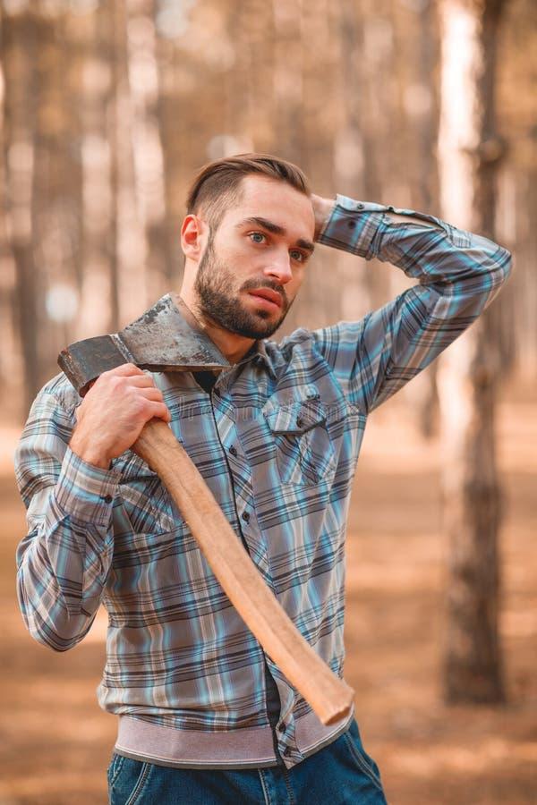 En grabb med en yxa i hans hals justerar hans hår i träna arkivfoton