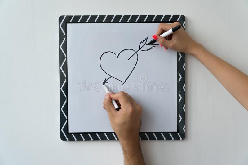 En grabb och en flicka drar en hjärta med markörer på ett vitt bräde En maskering och en kvinnlig hand mot ett vitt bräde med ett royaltyfria bilder