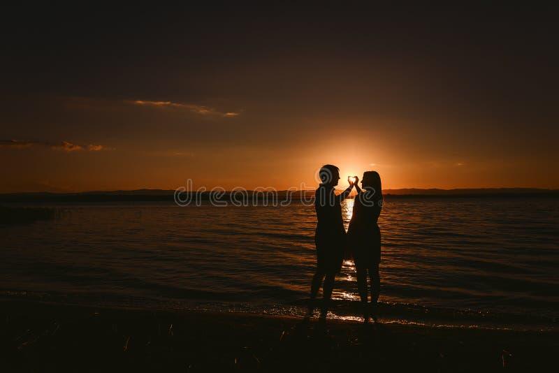 En grabb och en flicka gör en hjärta ut ur deras händer på havet på solnedgången royaltyfria foton