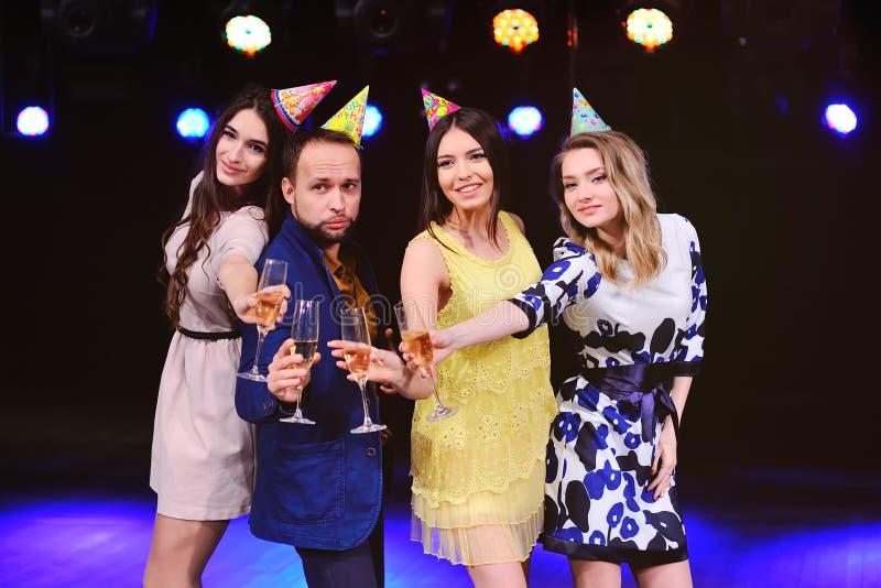 En grabb och tre flickor jublar och firar partiet i nattklubben fotografering för bildbyråer
