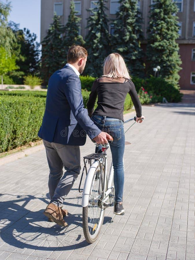 En grabb rider hans flicka på en cykel arkivbilder