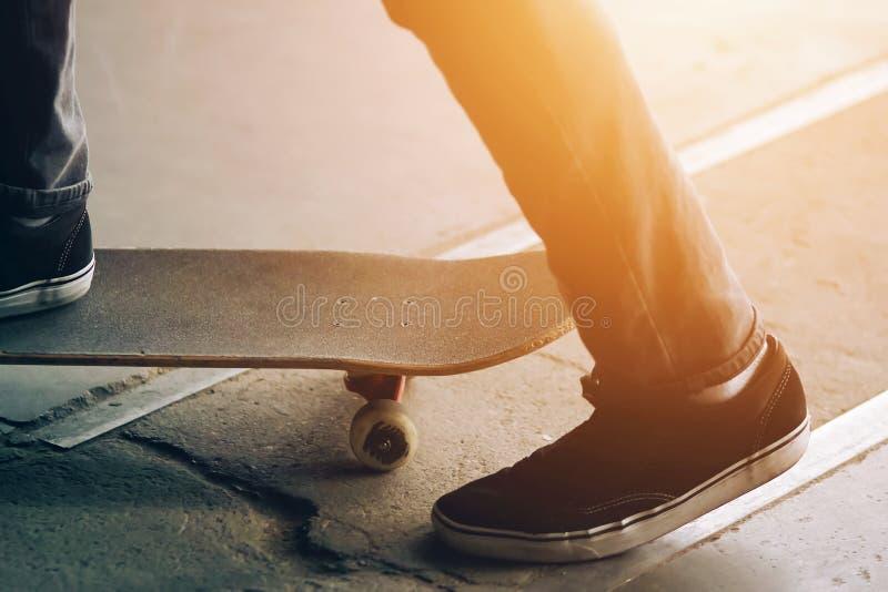 En grabb satte en fot på en skridsko, och annan skjuter av asfalten arkivfoto