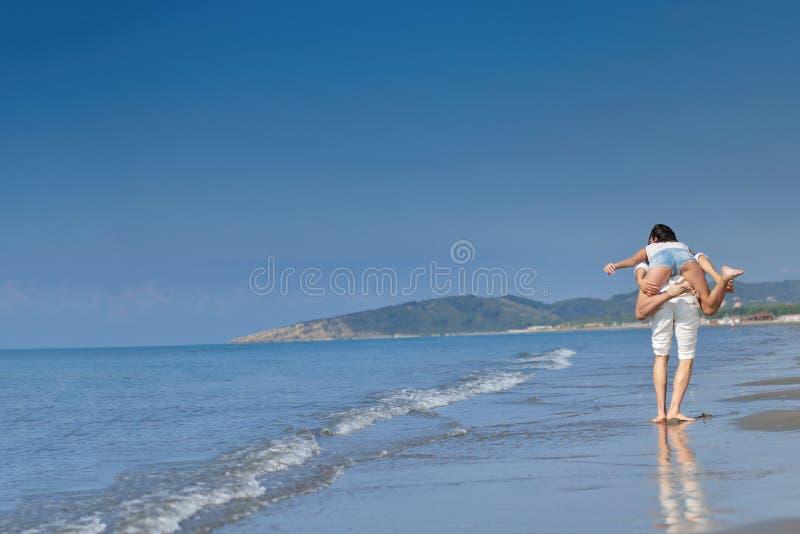 En grabb som bär en flicka på hans baksida, på stranden, utomhus royaltyfri fotografi