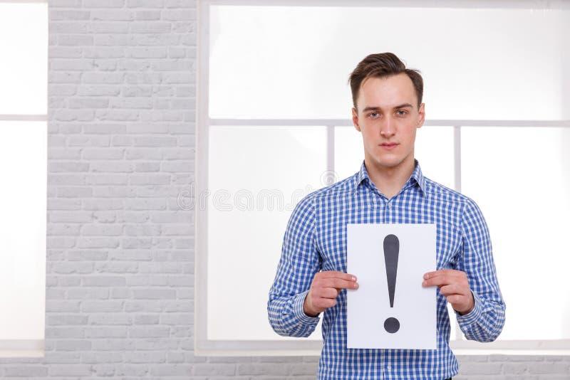 En grabb som rymmer ett ark med en utroppunkt, är den stående rätten på bakgrunden av fönstret arkivfoto