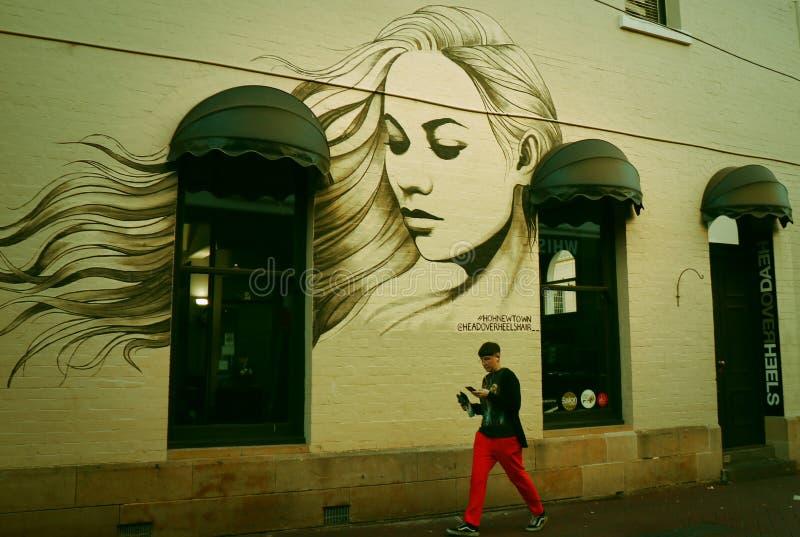 En graffitied hus-stående av en härlig kvinna på väggen arkivfoton