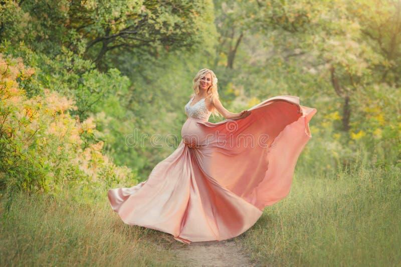 En gravid flicka för söt vår med ljust lockigt hår dansar i träna, är iklädd delikat långt elegant flöda arkivbilder