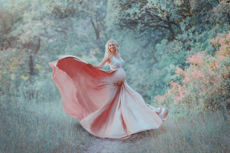 En gravid flicka för söt vår med ljust lockigt hår dansar i träna, är iklädd delikat långt elegant flöda arkivbild