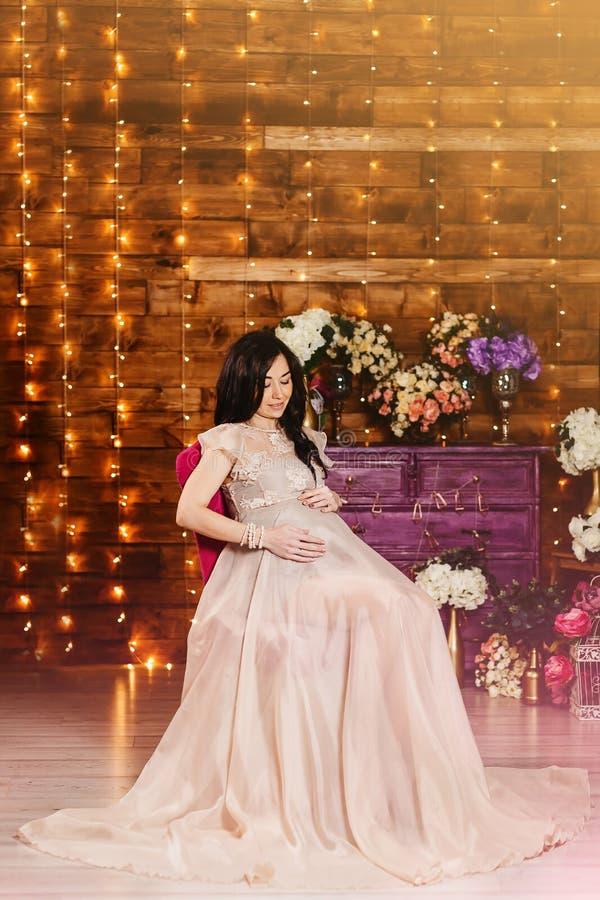 En gravid kvinna i en härlig lång kappa i studio royaltyfri bild