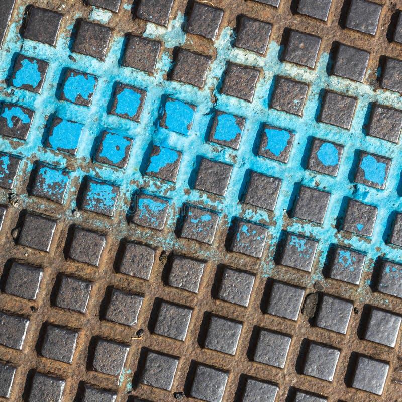 En gros plan d'une couverture de trou d'homme brune et bleue photos libres de droits