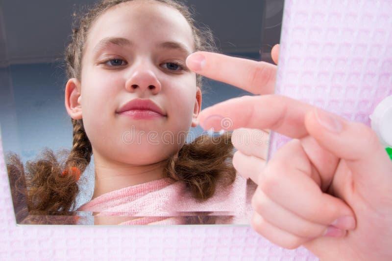 En gros plan, la fille regarde dans le miroir et tient une lentille sur son doigt pour améliorer la vision photo stock