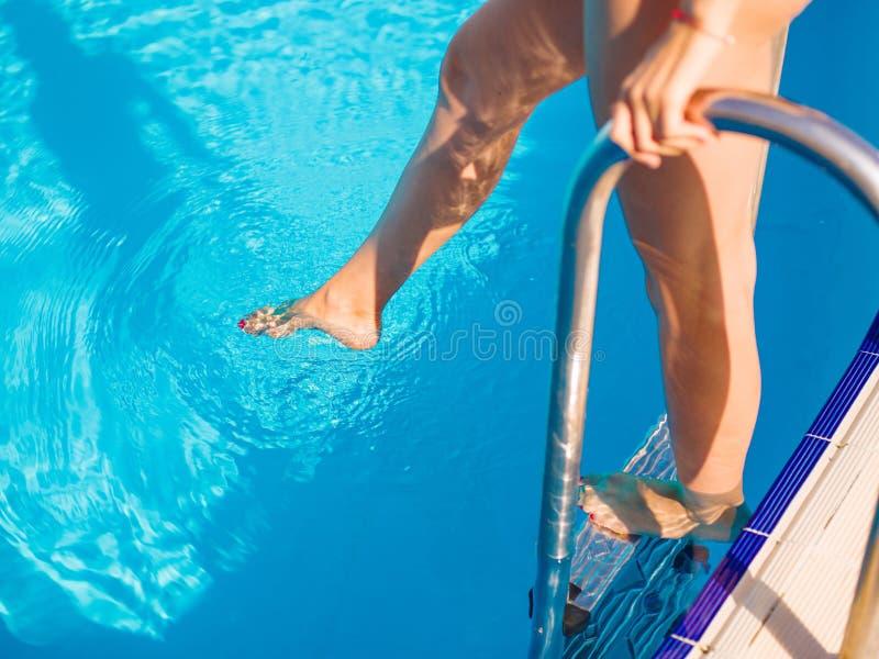 ` En gros plan s chaud, jambes sexy et bronzées de femme sur un fond de piscine Concept de piscine d'hôtel images stock