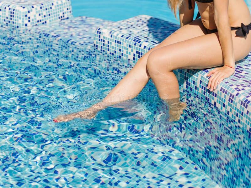 ` En gros plan s chaud, jambes sexy et bronzées de femme sur un fond de piscine Concept de piscine d'hôtel photographie stock libre de droits