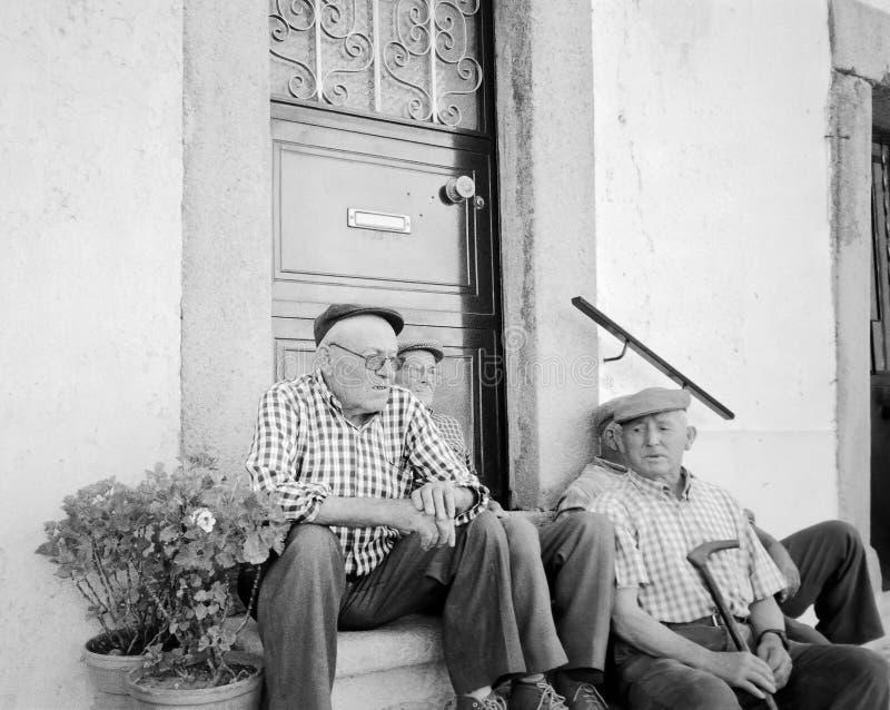 En grupp av äldre män som tillsammans sitter utanför husdörren, Portugal arkivbild