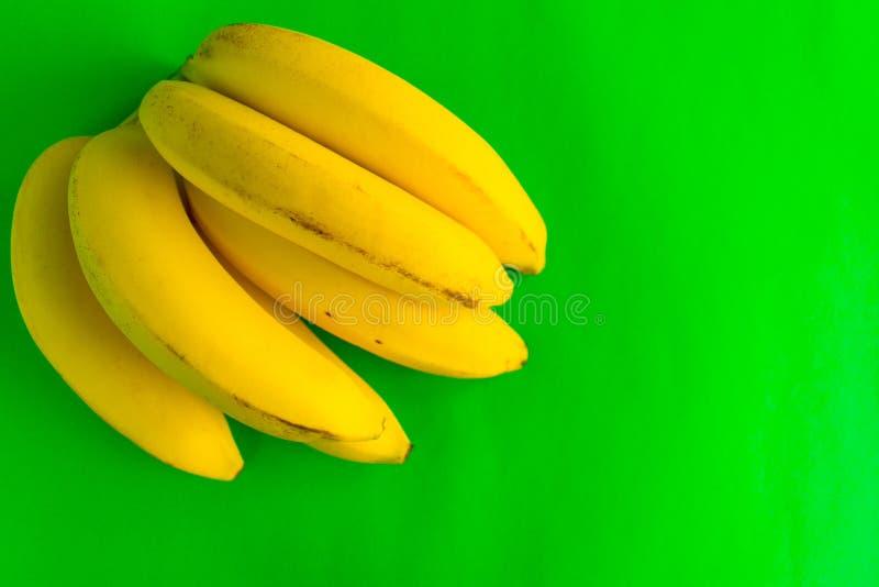 En grupp av bananer på ett ljust - grön bakgrund kopiera avst?nd royaltyfri bild