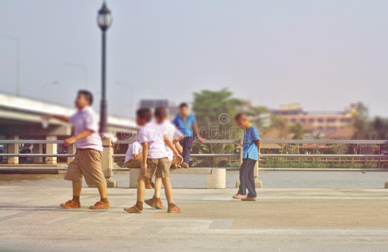 En grupp av barn i en vit skolalikformig och en blå himmel som kör längs floden arkivfoto