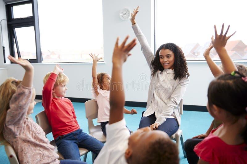 En grupp av begynnande skolbarn som sitter på stolar i en cirkel i klassrumet som lyfter händer med deras lärarinna, nära u arkivbilder