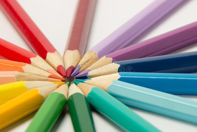 En grupp av blyertspennor vek i regnbågefärger i en cirkel på en whi royaltyfria foton