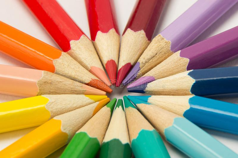 En grupp av blyertspennor vek i regnbågefärger i en cirkel på en whi royaltyfri fotografi