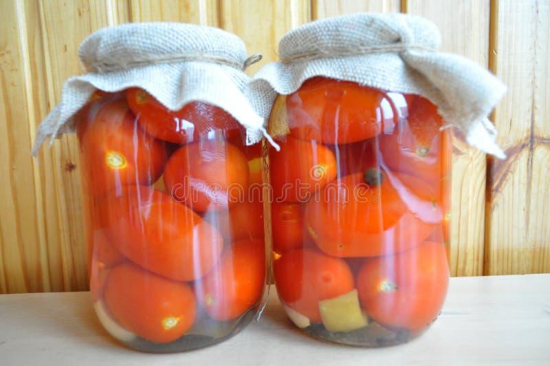 En grupp av cans med på burk tomater och gurkor royaltyfria foton