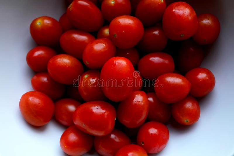 En grupp av Cherry Plum Red Shiny Tomatoes i en vit keramisk bunke på en träbakgrund royaltyfri fotografi