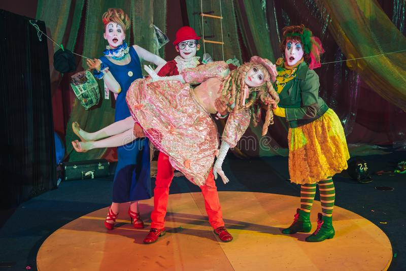 En grupp av clowner, en clownman som lyfts i hans armar en kvinna som beskriver en stationär docka fotografering för bildbyråer
