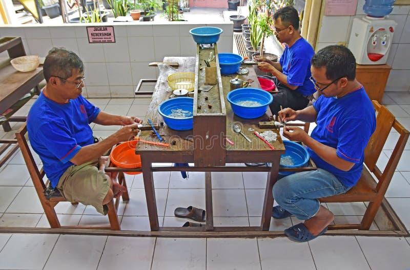 En grupp av den manliga tvagningen, lokalvård och att sätta för silversmed sista handlag på de rena silverprydnaderna royaltyfri fotografi