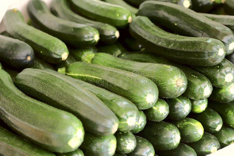 En grupp av den nya gröna zucchinin som staplas i rader Kantjusterat skott som är horisontal, närbild, sidosikt arkivfoton