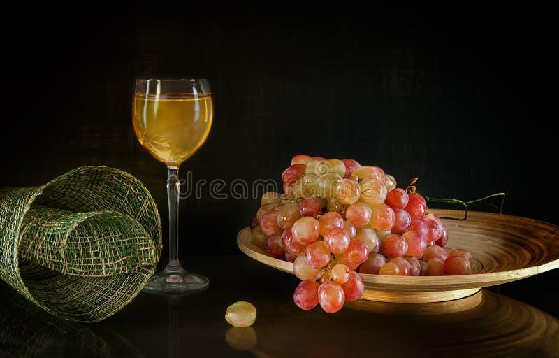 En grupp av druvor som ligger på en rund träplatta bredvid ett exponeringsglas av anseende för vitt vin på bakgrund med reflexion royaltyfri foto
