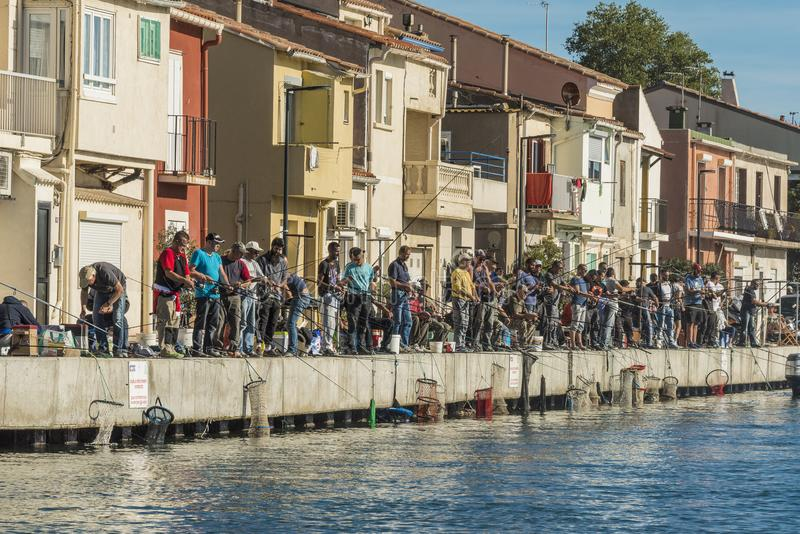 En grupp av entusiastiska fiskare i Sete, Frankrike arkivfoton
