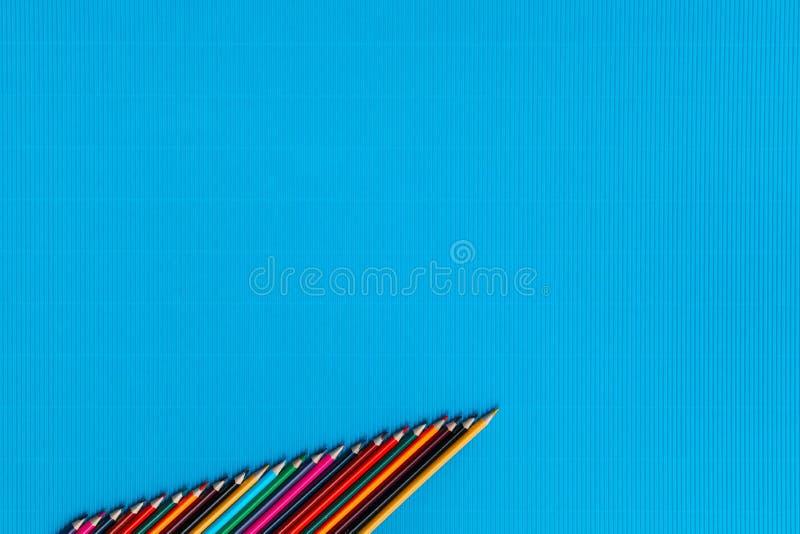 En grupp av färgpennor som ordnades i en stigande beställning på en blå bakgrund för havet som sköts från över, arrangera i rak l arkivfoto