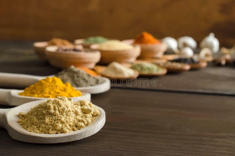 En grupp av färgrika kryddor på trätabellen royaltyfri foto