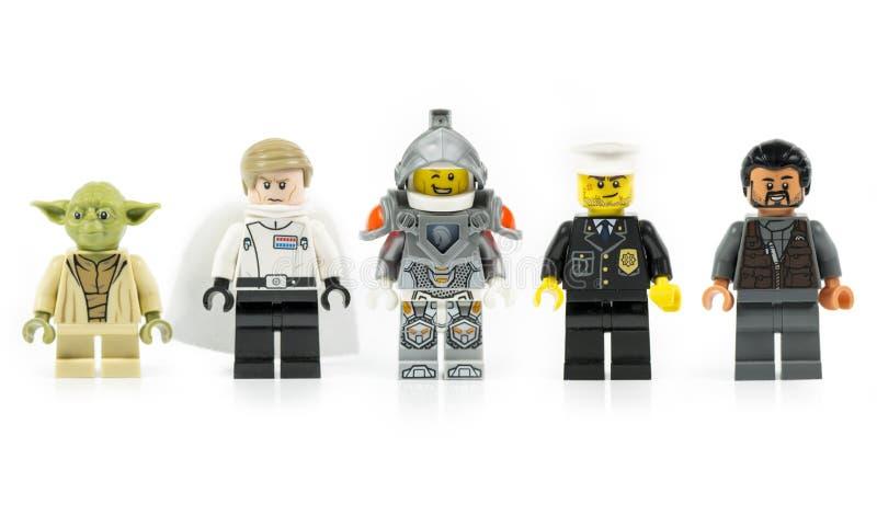 En grupp av fem olika Lego mini- tecken som isoleras på vit arkivfoto